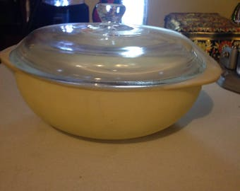 Covered pale yellow pyrex casserole dish