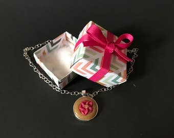 A yellow pendant necklace with a pink flower charm in a gift box