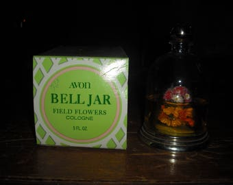 Avons Bell Jar is a decanter in the shape of a bell with flowers inside.