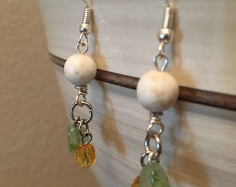 White dangle earrings with green and orange accent.