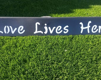 Love Lives Here black wood sign with white letters