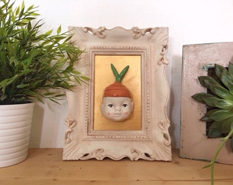 Jide. Head of carrot, ceramic face.