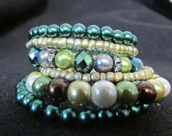 Memory wire wrap bracelet in cream and green metallic beads.