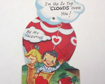 Vintage Mechanical Valentine Greeting Card with Cute Boy and Girl in Hot Air Balloon in the Clouds