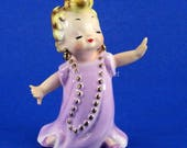 Little Girl Playing Dress Up Purple Dress, Gold Beads, Blond Ponytail George Imports