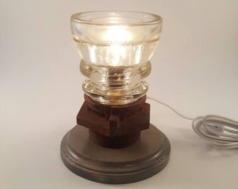 Glass insulator lamp with rusty industrial and wooden base.