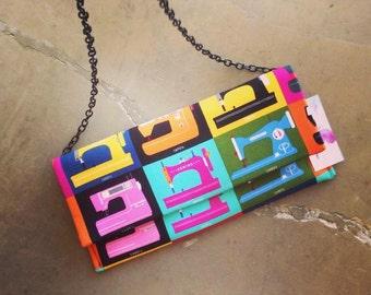 Bold print, multicolored, retro themed clutch purse.