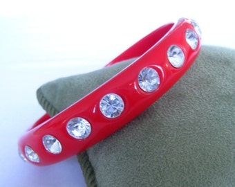 "Red Plastic & Rhinestone Bangle Bracelet. 22 Clear Bright Rhinestones (6 mm each) Set into the Bracelet's Entire Perimeter.  1/2"" Wide."