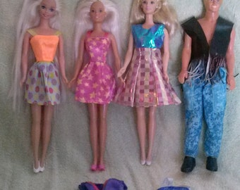 Ken and three Barbies with clothes.