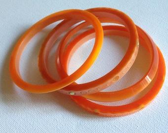 Bangles - collection of four vintage orange plastic bangles