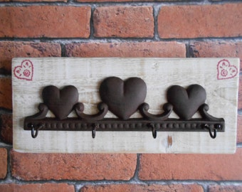 Cast Iron Hearts with Hooks on Distressed Wood with Heart Motives