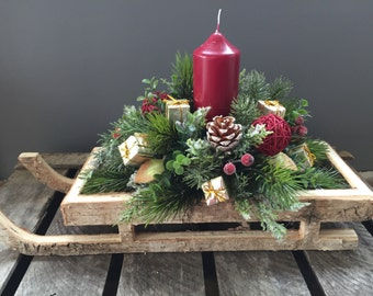 Christmas Floral arrangement on a wooden sleigh with burgundy candle and burgundy and gold accesories, Christmas centepiece.