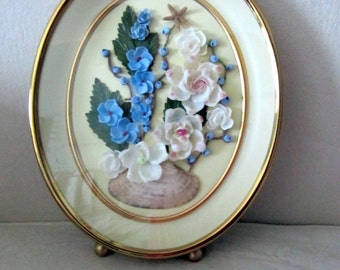 Gold shadow box frame with shell flowers