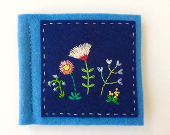 blue wool felt needle book with pretty hand embroidered flowers in rainbow colors