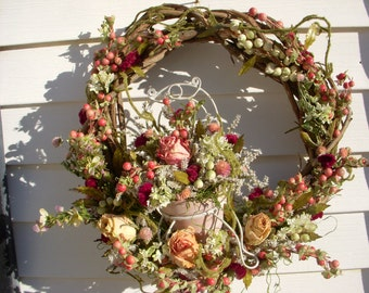 Victorian garden themed wreath made from natural WV grapevine with a vintage look garden chair and decorated with dried and other flowers