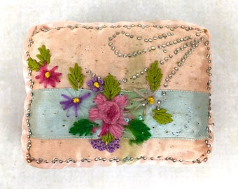 vintage or antique satin pincushion with embroidery and pin design