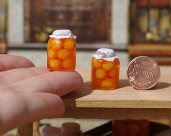 Canned tangerines in miniature banks. Miniature pickled fruit jars for a doll house. Miniature Mandarins. On a scale from 1/12.