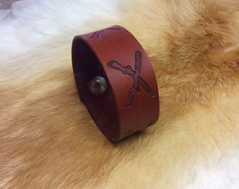Leather cuff bracelet with steamed crossed rifle throughout