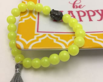 Neon Yellow beaded flexible bracelet with a Pewter Buddha Head and Gray Tassel.