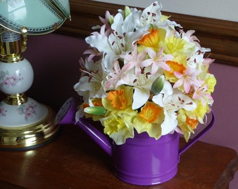 A little watering can full of spring flowers, lilies, daffodils, Peruvian lilies