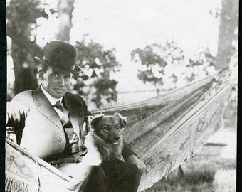Man in Bowler Hat Sitting On HAMMOCK with His BEST FRIEND Dog Photo Postcard circa 1910