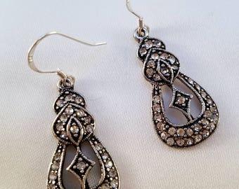 Bedazzled silver dangle earrings.