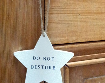 Do not disturb star shape hanging door sign in natural wood or matt white finish with hand stamped lettering and natural jute string