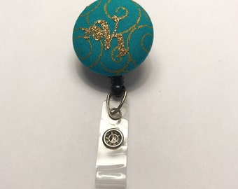 Badge reel, gold glitter K on teal and gold fabric button badge reel