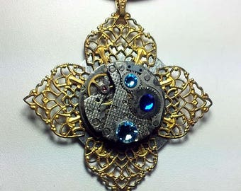 Steampunk  pendant, 2 dials, ,  gears,blue  Swagoldy filigree, Swarovski chrystal cabs.Side 1 mecanism, side 2 goldy Buddha