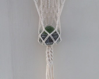 Intricate macrame hanging planter made with cotton twine and wooden dowel