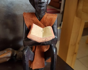 Large African man with book in dark wood