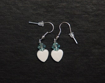 White polymer clay heart dangle earrings with translucent blue-green bead and stainless steel hooks.