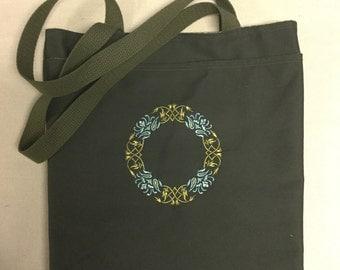 Medallion Embroidered on dark olive green bag.