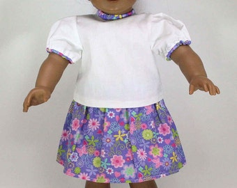 A complete 18 inch doll outfit including white blouse with floral trim, pink capris and skirt, pink jelly shoes and a scrunchy for her hair