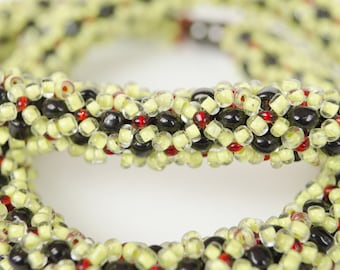 Handmade necklace made of transparent sand beads with red interior, transparent with yellow inside and glossy black