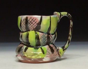 Bright green and pink wavy mug with stripes of glazes