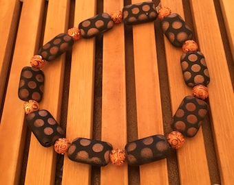 7.5 inch copper and black dotted beaded stretch bracelet.