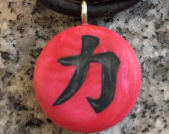 "Japanese kanji symbol for ""STRENGTH"" hand carved on a polymer clay red pearl color background. Pendant comes with a FREE necklace"