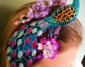 Turquoise peacock fascinator with flower details. Sold, but available with purple peacock.