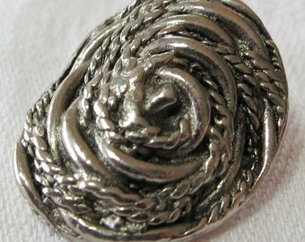 """1X1"""" oval button, metal, silver toned. Abstract design, coiled chord on curved top, probably hand made. Self shank. Lovely. KK16.1-3.13-2."""