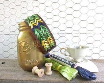 Rita cuff. Brown leather cuff woven in chevron pattern of emerald green, true blue and bright yellow vintage Swistraw by Ruby Buffalo.