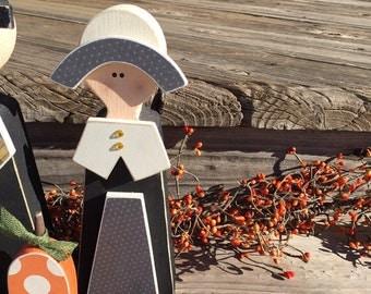 Wood pilgrims and pumpkin Thanksgiving decor fall table