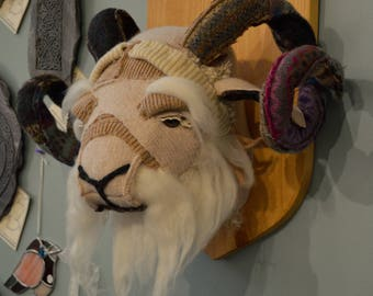 Large textile rams head mounted on a wooden plaque