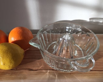 Clear glass juicer with handle and spout.