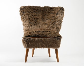 Faux fur Coctail Chair with genuine leather piping line.