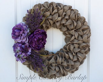 Stunning earth tone burlap wreath accented with purple peonies, one purple hydrangea and beautiful purple spray