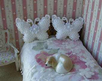 One pair of dollhouse bed cushions. 1/12 scale. Butterfly shaped. Pale ivory with white flower and pearl trim. Handmade.