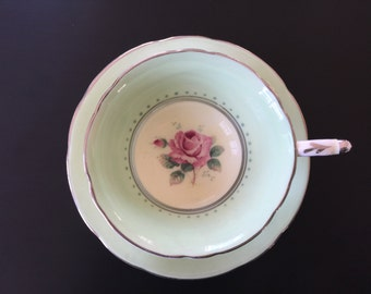 A Paragon teacup and saucer in peppermint green with single pink Rose motif