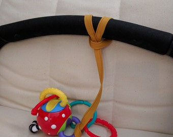 Toy tethers, straps, fasteners, attach toys to pushchair  / pram / buggy.