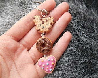 Sweets Keychain - a Teddy Bear Chocolate Chip Cookie, a Donut with Chocolate Icing, a Pink Heart Shaped Cookie With Colorful Sweets